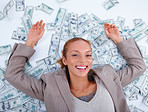 Successful businesswoman lying flat out on money