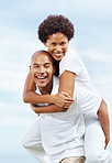 Joyful young man carrying girlfriend on his back