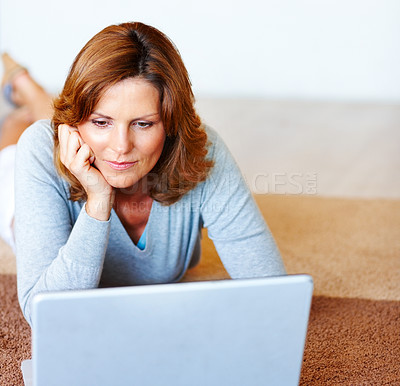 Buy stock photo Cute young lady using laptop while lying on floor