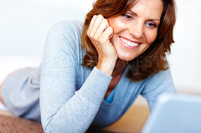 Buy stock photo Happy mature woman using laptop while lying on flo