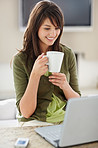 Beautiful female working on a laptop , having coffee at home