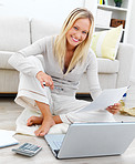 Happy woman sitting on floor and using laptop by sofa