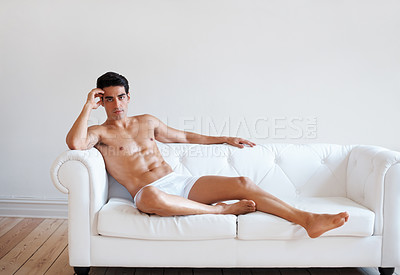 Buy stock photo Portrait of a muscular young guy in underwear posing on couch at home