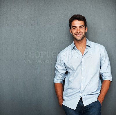 Buy stock photo Handsome man casually leaning against the wal