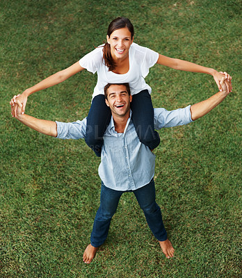 Buy stock photo Pretty woman sitting on her boyfriend's shoulders, both smiling up at the camera against a grassy background