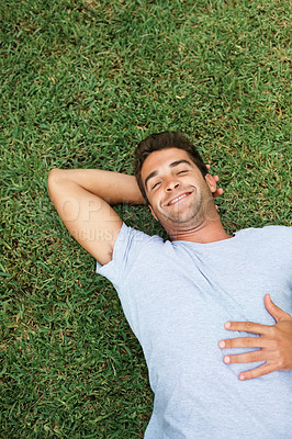 Buy stock photo Flirtatious man laying on the grass