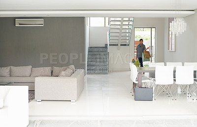 Buy stock photo Stylish woman arriving home and walking into her dining room and living room of her modern home