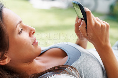 Buy stock photo Pretty woman lying down and looking at Smartphone