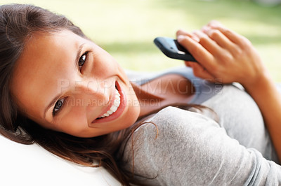 Buy stock photo Pretty woman lying down and holding a Smartphone