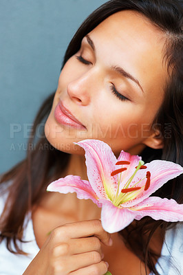 Buy stock photo Head shot of pretty woman holding a flower against blue background