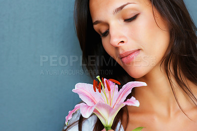 Buy stock photo Head shot of pretty woman looking down at flower against blue background