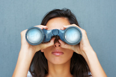 Buy stock photo Pretty woman looking through binoculars against blue background