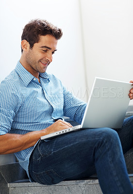 Buy stock photo Shot of a handsome young man working on a laptop while sitting on staircase