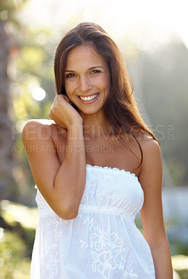 Buy stock photo Portrait of a beautiful young woman standing outside and smiling on a summer day
