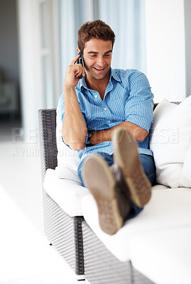 Buy stock photo Shot of a happy young man talking on mobile phone while sitting on couch