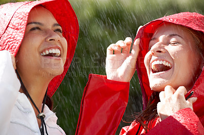 Buy stock photo Two excited girlfriends wearing raincoats enjoying the rain - Outdoor