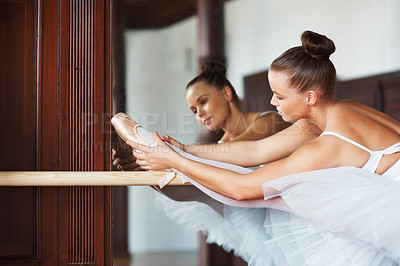 Buy stock photo Portrait of a ballerina practicing a stretch at barre in front of a mirror