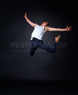 Buy stock photo Full length of a young male ballet dancer performing against black background