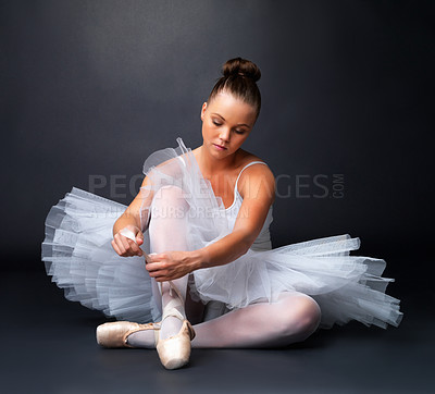 Buy stock photo A beautiful ballerina sitting down fitting her ballet shoe, against a shadowy background