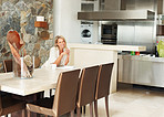 Happy female in dining room by kitchen in a modern house