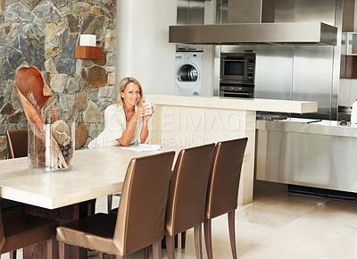 Buy stock photo Open plan kitchen with portrait of a mature woman sitting at dining table in a modern house