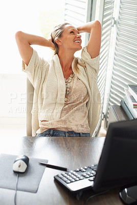 Buy stock photo Happy mature female executive relaxing in front of computer at work desk