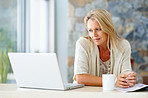 Middle aged woman with coffee cup looking at laptop screen