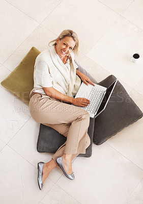 Buy stock photo Top view of a cheerful middle aged woman with laptop and cushions lying on floor