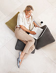 Pretty relaxed woman using laptop on floor