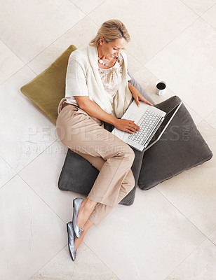 Buy stock photo Top view of a pretty relaxed middle aged woman using laptop on floor