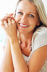 Relaxed blue eyed woman smiling , hands clasped