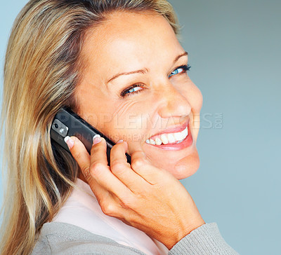 Buy stock photo Closeup portrait of a friendly mature woman using a cellphone against blue background