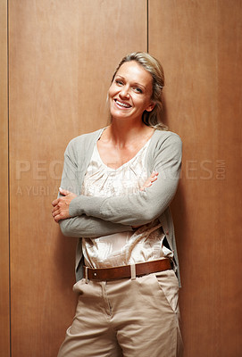 Buy stock photo Portrait of a mature business woman smiling with hands crossed against wooden background