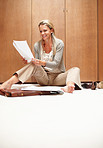 Casual mature woman sitting on floor and doing paperwork