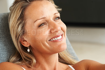 Buy stock photo Closeup of a relaxed mature woman smiling over a thought