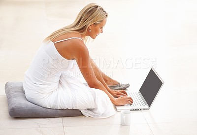 Buy stock photo Side view of a mature woman sitting on floor and using laptop