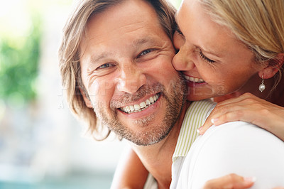 Buy stock photo Closeup of a mature woman kissing a happy guy tenderly with a smile