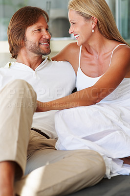 Buy stock photo Portrait of a happy relaxed couple looking at each other and smiling