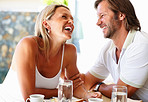 Happy mature man and woman having fun at dining table