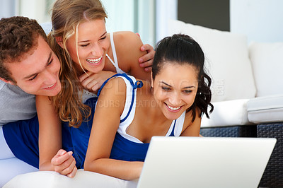 Buy stock photo Portrait of young friends in playful mood at home while using laptop