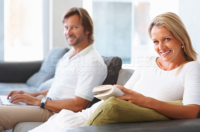 Buy stock photo Portrait of a happy mature woman reading a book with man using laptop at home