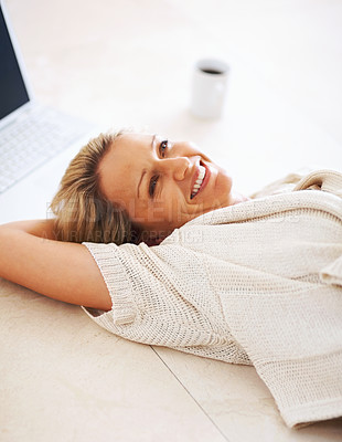 Buy stock photo Portrait of a smiling middle aged woman lying on floor by laptop and tea cup