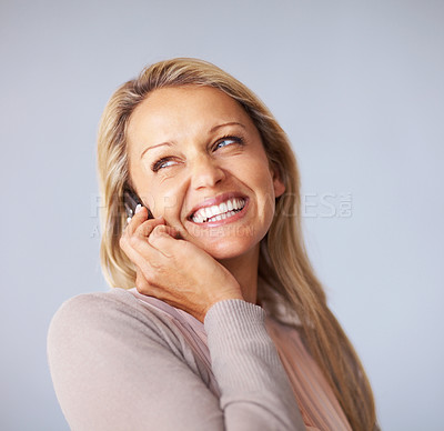 Buy stock photo Portrait of a happy mature woman using a cellphone against blue background