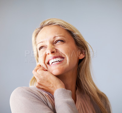 Buy stock photo Thoughtful middle aged woman smiling in her thoughts against colored background