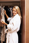 Happy mature woman selecting clothes near wardrobe after a bath