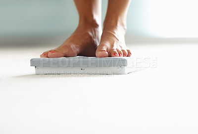 Buy stock photo Low section closeup of a woman's feet on weighing scale