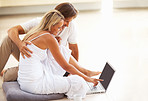 Happy relaxed mature couple sitting on floor and using laptop