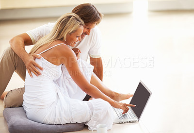 Buy stock photo Side view of a happy relaxed mature couple sitting on floor and using laptop