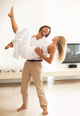 Buy stock photo Portrait of a loving man carrying a woman in his arms at home