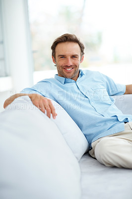 Buy stock photo Portrait of a casual young man sitting on couch and smiling - Indoor